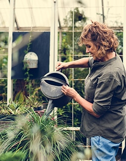 Woman watering fresh shipped dirt and plants
